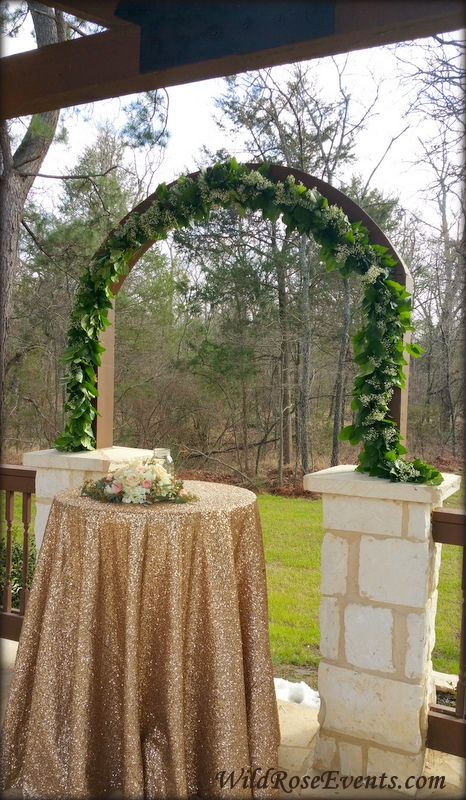 Wild-Rose-Events-green-garland-and-babies-breath-on-the-arch-at-Poetry-Springs-Events-with-a-Unity-table-and-flowers